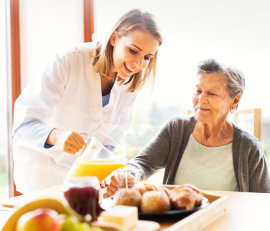 caregiver serving juice to elderly woman