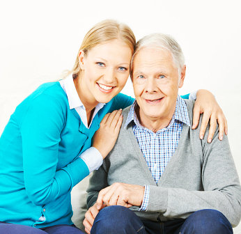 caregiver hugging an elderly man