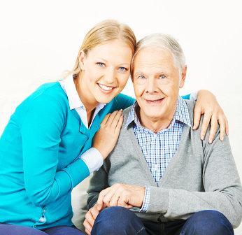 caregiver hugging an elderly man