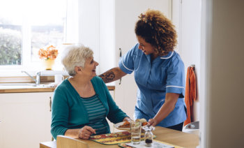 caregiver serving food to an elderly woman