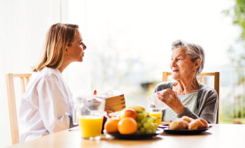 caregiver and elderly woman talking at each other