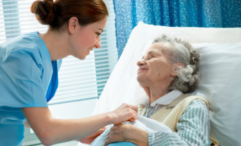 caregiver smiling to an elderly woman