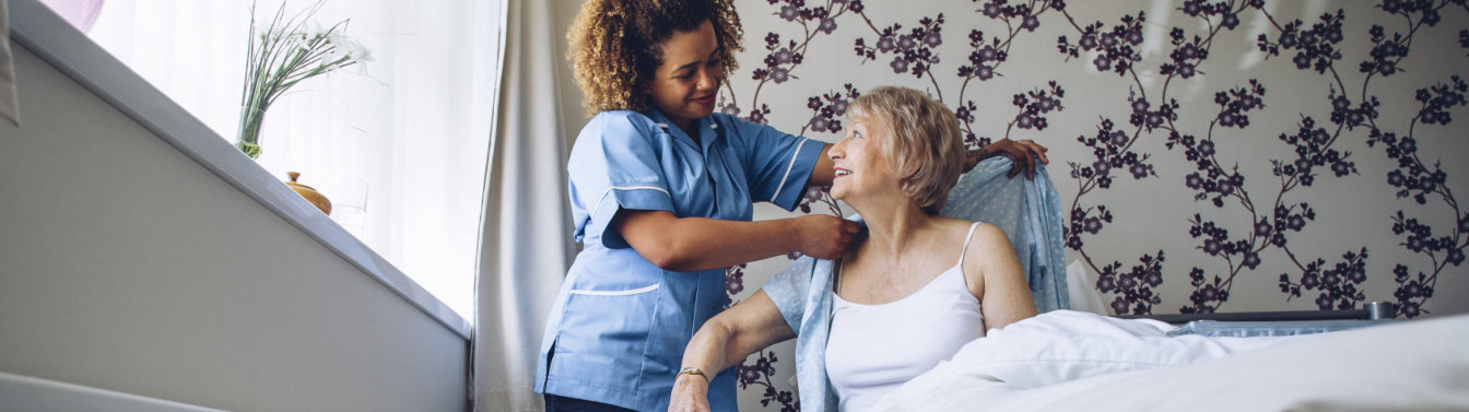 caregiver assisting an elderly woman in dressing up