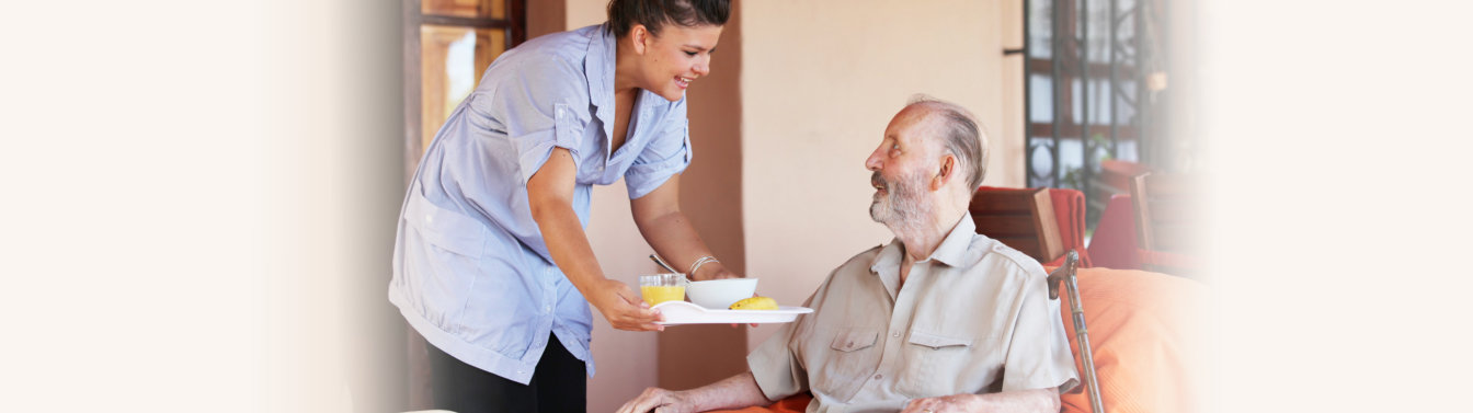 caregiver giving food to an elderly woman