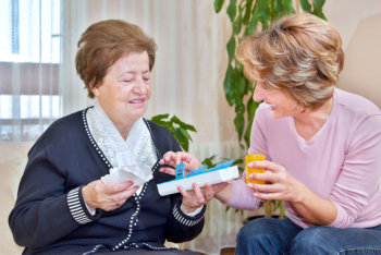 caregiver giving medicine to elderly woman