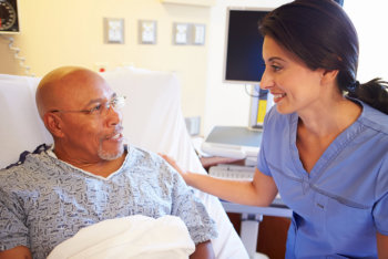 caregiver smiling to an elderly man lying on his bed