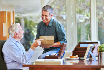 elderly man giving an envelope to a man