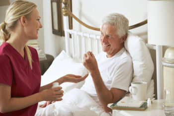 caregiver giving medicine to an elderly man lying on bed