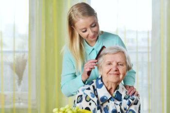caregiver grooming an elderly woman