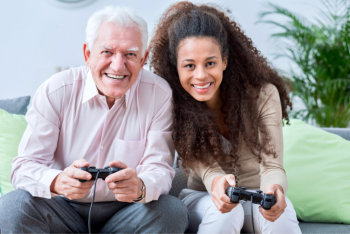 caregiver and elderly man playing a game