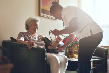 caregiver taking the blood pressure of an elderly woman